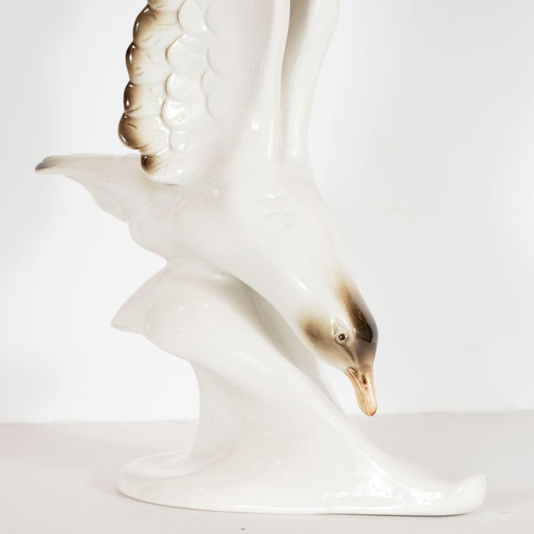 This elegant sculpture was realized by the esteemed porcelain company, Royal Dux, and hand fabricated in Czechoslovakia, circa 1950. It features a cream colored seagull with touches of sable brown on its finely articulated wings and a mocha hued