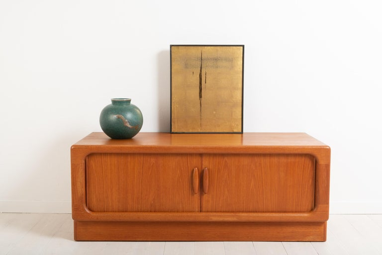 Sideboard in teak made by Dyrlund in Denmark. 1960s sliding doors. The sideboard is made from teal and marked with a label. Good vintage condition consistent with age and use. Minor traces of wear.