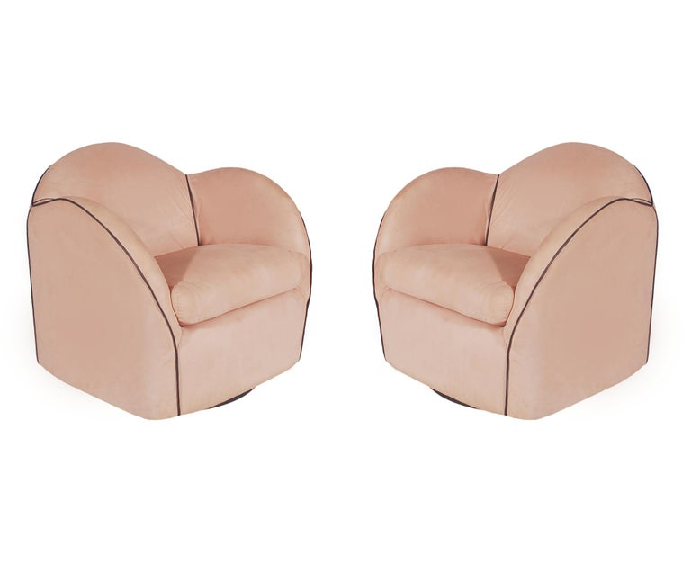 A very chic pair of swiveling club chairs from the late 1970s. These are high quality well made chairs. The pink suede upholstery is tired and soiled. Chair padding is excellent so light reupholstery is recommended. We currently have 4 chairs total,