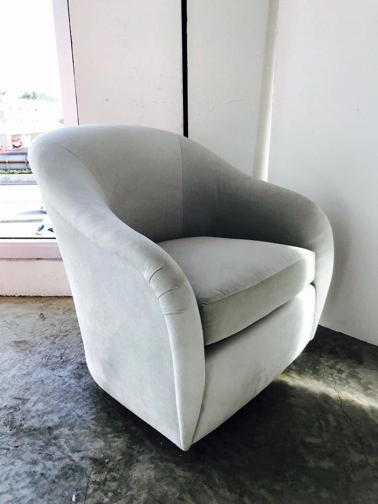 Gorgeous Mid-Century Modern lounge chair with swivel base design. Chair has barrel back form with elegant curved and tapered sides. Newly upholstered in light grey suede leather with reversible zippered seat cushion and original Interior Crafts