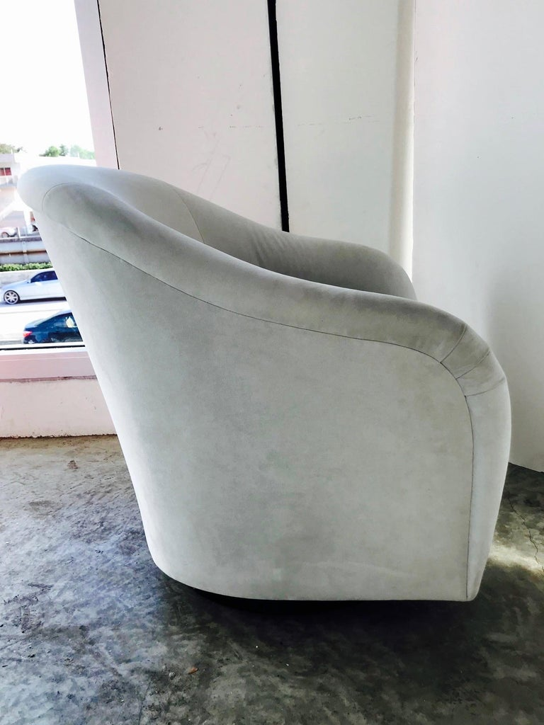 Gorgeous Mid-Century Modern lounge chair with swivel base design. Chair has barrel back form with elegant curved and tapered sides. Newly upholstered in light fine grey velvet with reversible zippered seat cushion and original interior crafts label.