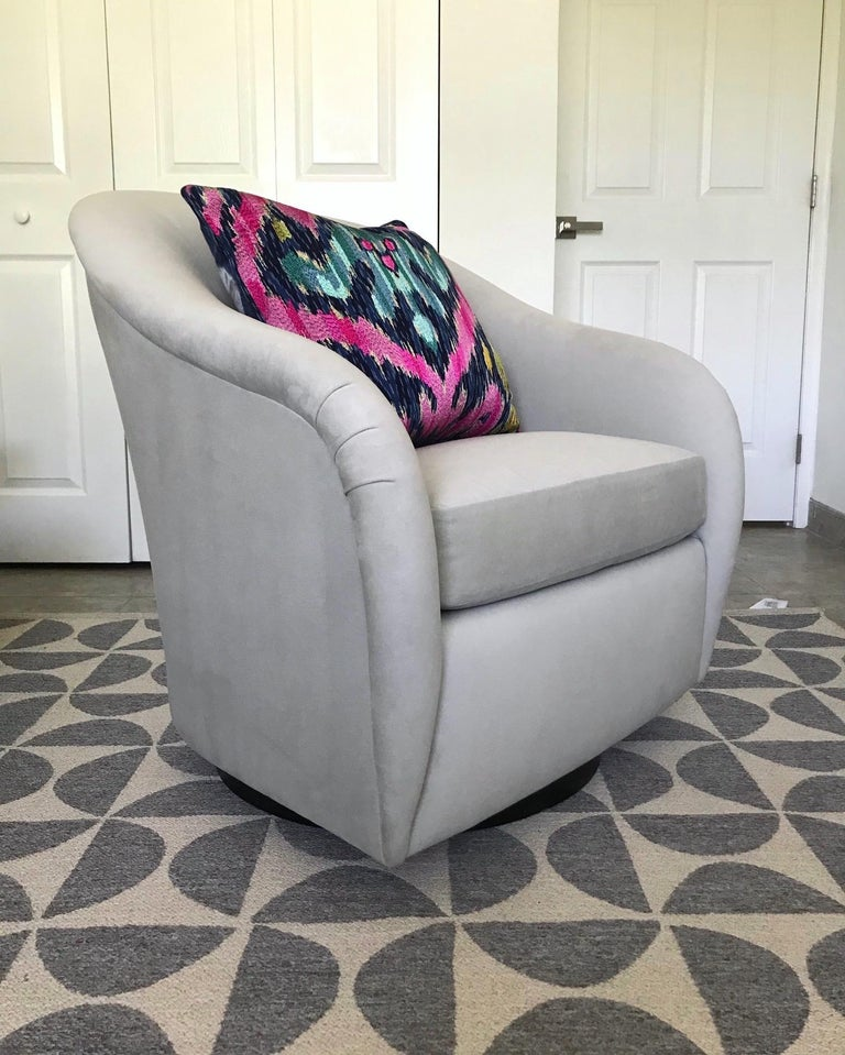 1970s Mid-Century Modern lounge chair with swivel base design. The chair features sleek lines with an elegant curved frame, tapered sides with pleated armrests, barrel back detail, with a round swivel base in ebonized bentwood. Newly upholstered in