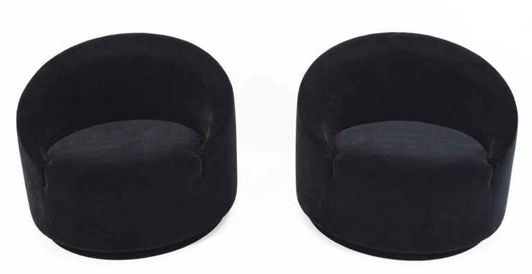 A really very nice pair of cool looking swivel tub chairs upholstered in black mohair by Maharm.