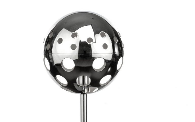Polished chrome table lamp with spherical shade pierced with holes to allow the light to exit. This gives a very decorative effect in the room. The top of the sphere is removable to replace the bulb.