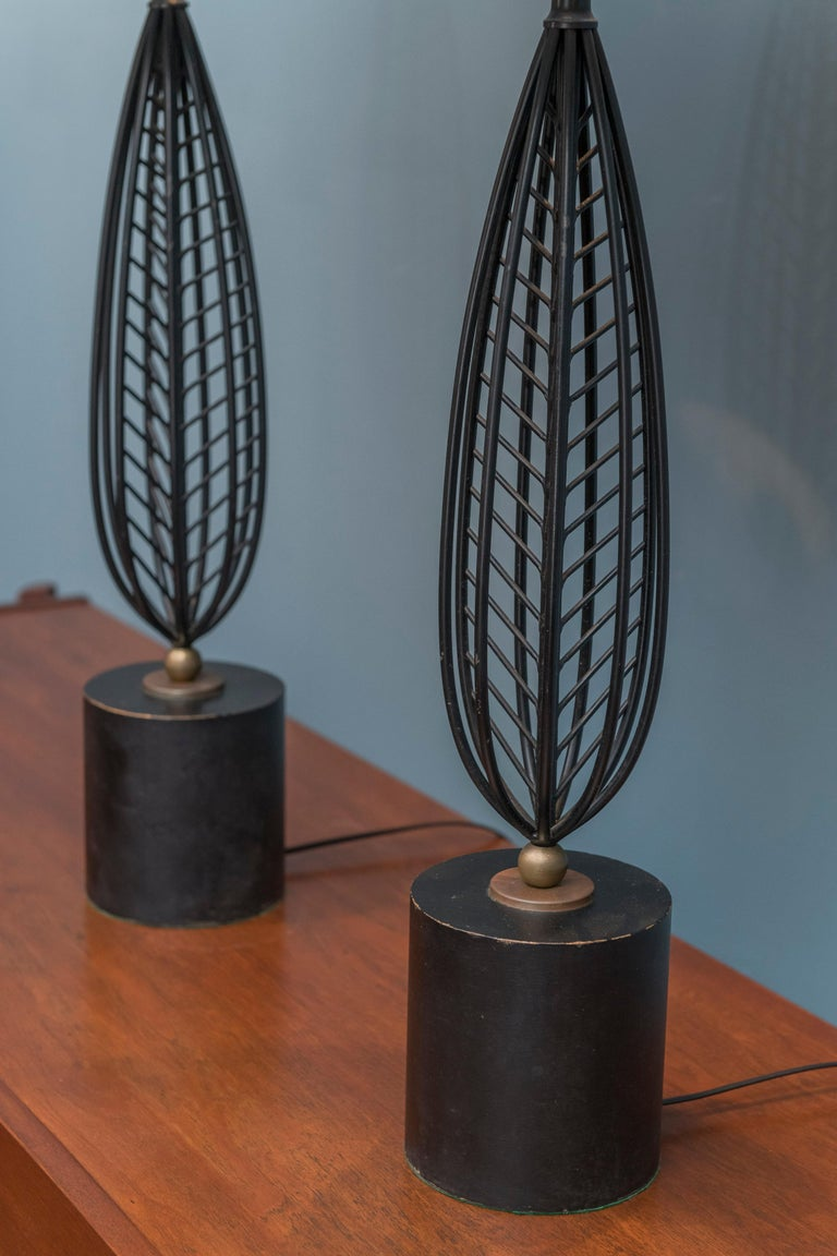 Mid-Century Modern table lamps made from painted black steel with gold accents on wood bases. Newly re-wired and restored. Height to the socket 27
