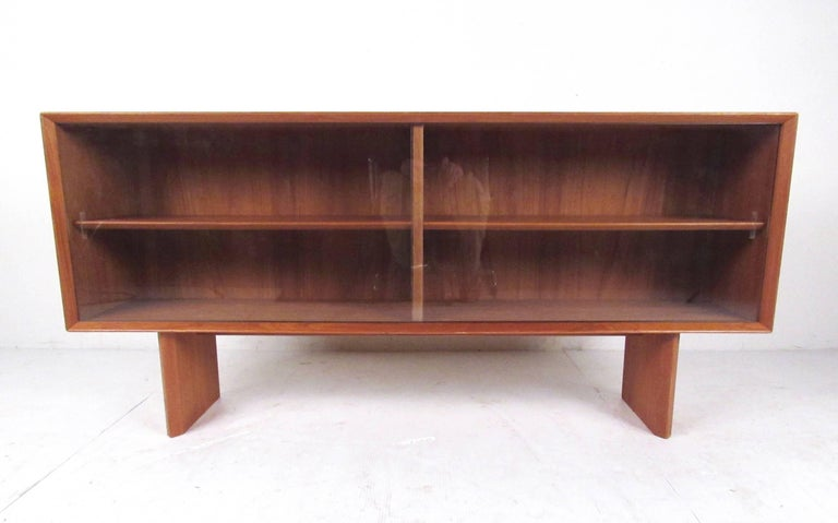 This Scandinavian teak book case by Falster offers adjustable shelf storage behind sliding glass doors. Danish modern design showcased with the rich Teak finish of the piece. Perfect display storage shelf for home or business use. Please confirm