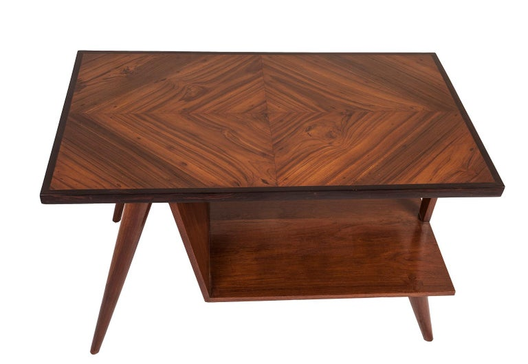 A Mid-Century Modern teak wood coffee table with a rosewood border. Great use of the wood grains on the top. Tapered legs. Lower shelf measures 10