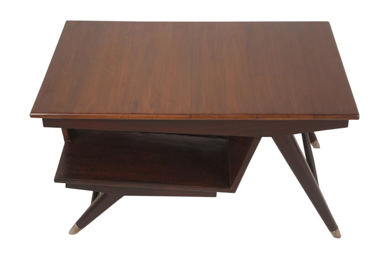 Mid-Century Modern teak coffee or cocktail table with an angled lower shelf for magazines or books. Brass feet on splayed legs and a carved harlequin design side support.