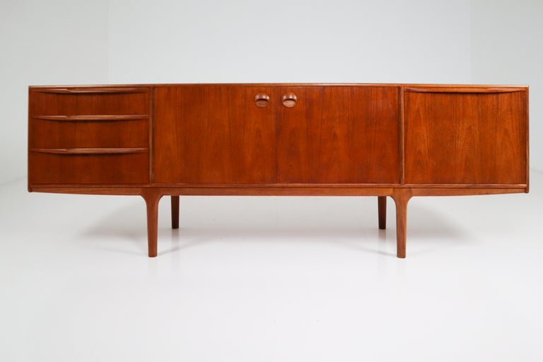 This beautiful vintage modern sideboard features plenty of room for storage within its four drawers and two large storage compartments hidden by cabinet doors. Sleek two-tone design with unique carved pulls and tapered legs adding to the allure.