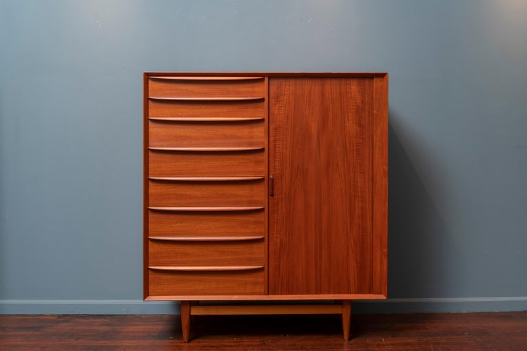 Mid-Century Modern teak gentleman's chest or tall dresser for Falster, Mobelfabrik Denmark.  Featuring 17 drawers with 8 on the left and another 9 hidden behind a tambour door. Newly refinished and ready to enjoy.