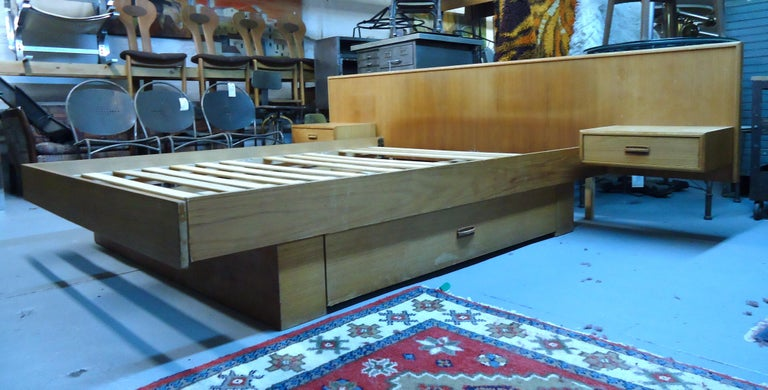 This stylish Danish modern queen size bed features built in headboard, floating end tables and dual drawer storage beneath the mattress. Versatile storage mixed with midcentury style makes this bed a wonderful addition to any home.  Please confirm