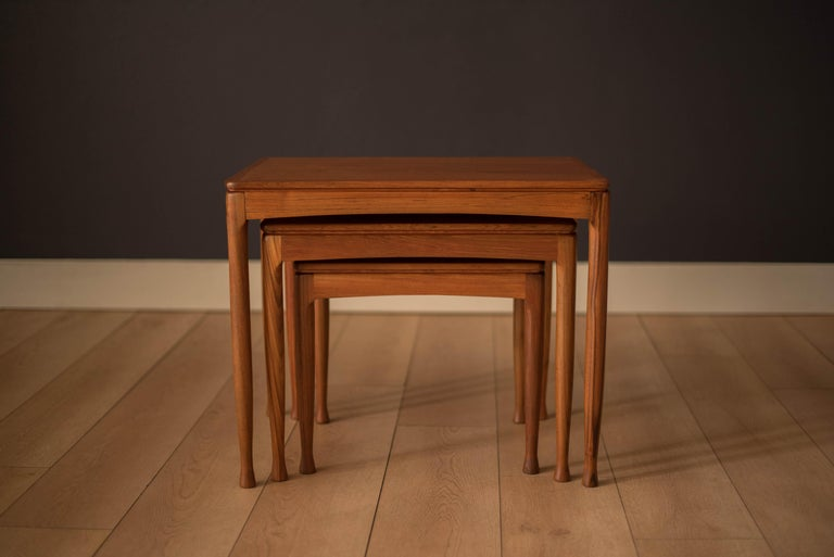 Vintage set of nesting tables in teak, circa 1960s. Designed with slender contoured legs and a modern classic aesthetic. This set includes three separate end tables in variable sizes that cleverly stack underneath each other making it perfect for
