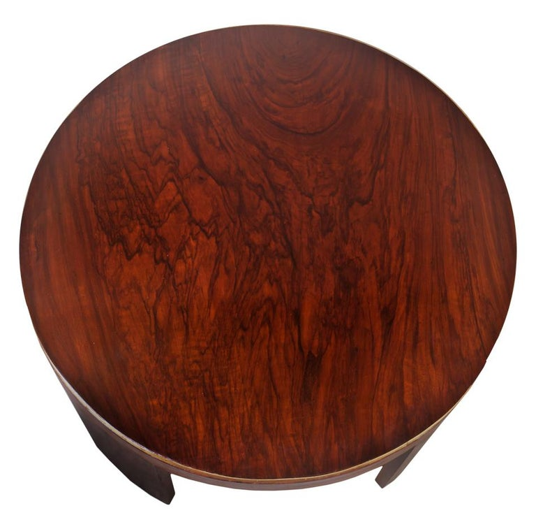 Mid-Century Modern round teak wood coffee or drinks table with brass border along the top, and tapered legs. European.
