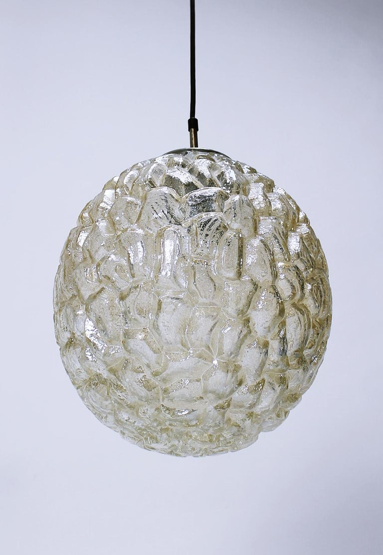 A beautiful and large oval shaped pendant light fixture by Glashütte Limburg, circa 1970s. Featuring a wonderful textured amber colored toned glass shade resembling ice crystals, this midcentury vintage lamp illuminates beautifully, casting a golden