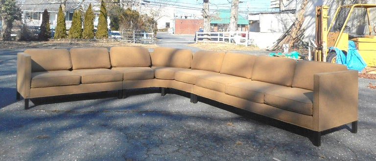 This impressive vintage modern sectional sofa consists of three separate pieces. A straight line midcentury design that boasts overstuffed removable cushions covered in a plush tan upholstery. This well made sofa by Dunbar sits on stubby black wood