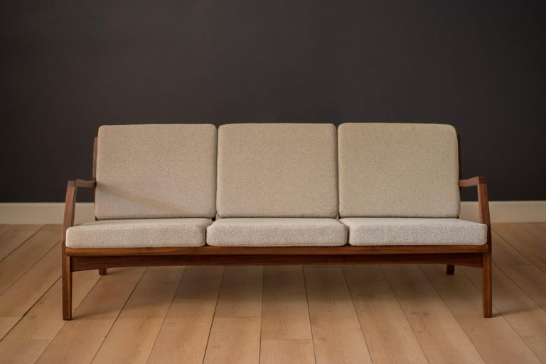 Vintage three-seat sofa constructed of solid walnut, circa 1960s. This piece has been professionally reupholstered in a nubby light grey boucle fabric supported by brand new Pirelli webbing. Features a sculptural walnut frame that can be displayed