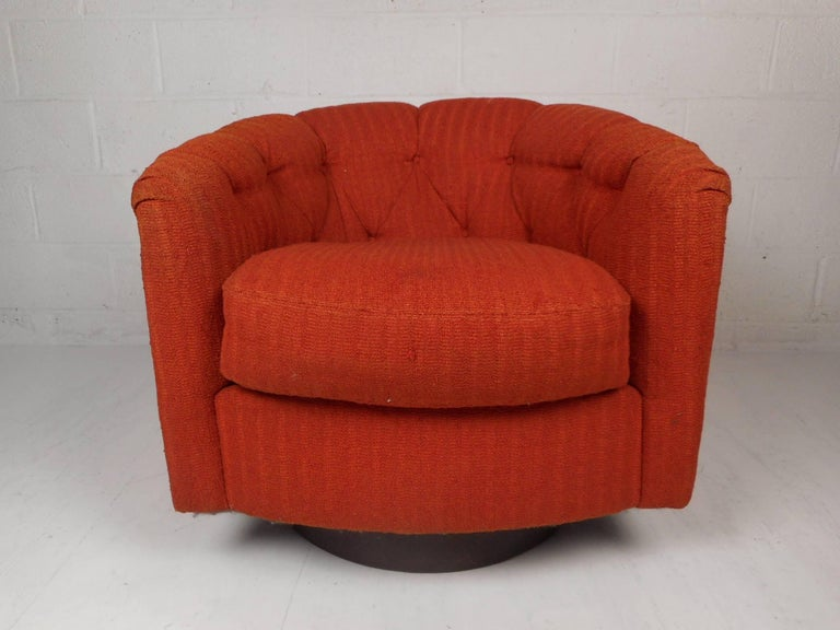 This beautiful vintage modern lounge chair has the ability to swivel and tilt with its versatile round walnut base. This wonderful chair is covered in plush orange upholstery and has an overstuffed removable cushion. Sleek design with a tufted