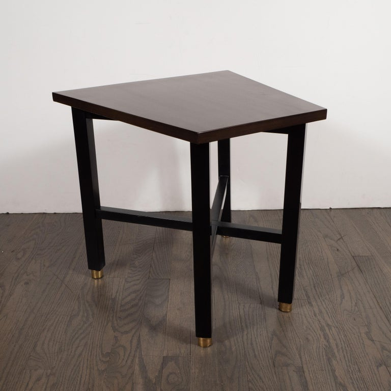 Designed by Dunbar and handcrafted in Berne, Indiana, this elegant side table was realized in the United States circa 1950. Featuring a hand rubbed walnut trapezoidal top and ebonized rectangular legs that sit on brass sabots, this piece is a study