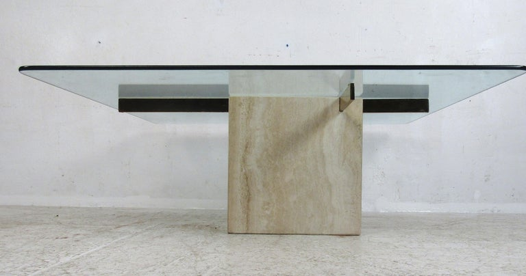 This stunning vintage modern Artedi coffee table features a thick square glass top with a travertine base. Sleek design with two brass supports fitted inside the travertine base holds the large glass tabletop. This elegant piece makes the perfect