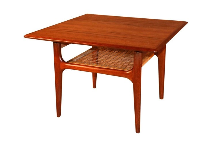 A beautifully crafted, Danish, two-tier, teak and cane table designed by Trioh Mobler, circa 1960s. This table features a sturdy two tier design with the bottom tier strongly supported by original woven cane. The second cane shelf adds additional