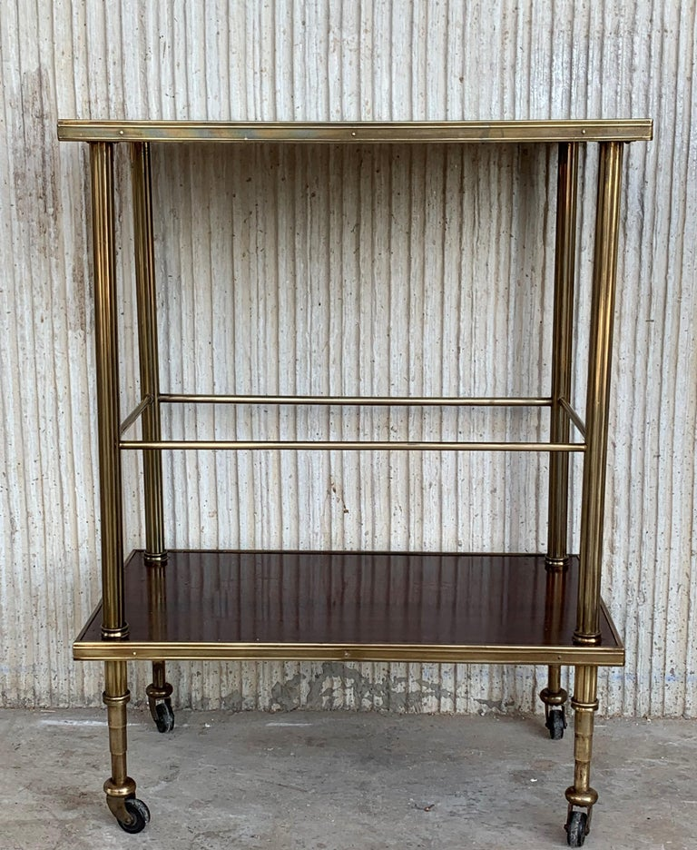 Mid-Century Modern two-tier brass and mahogany veneer glass side table in Maison Jansen style with fluted brass legs and wheels.