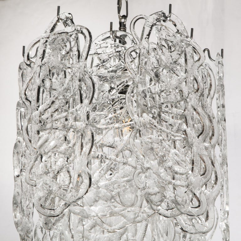 This sophisticated chandelier was realized in Murano, Italy the island off the coast of Venice renowned for centuries for its superlative glass production, circa 1970. It features two tiers of hand blown Murano translucent Murano glass consisting of