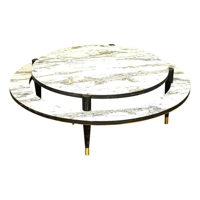 This round, Mid-Century Modern coffee table features two-tiers embellished with marbleized white Formica surfaces. The large-scale table rests on black painted legs capped with brass foot details.