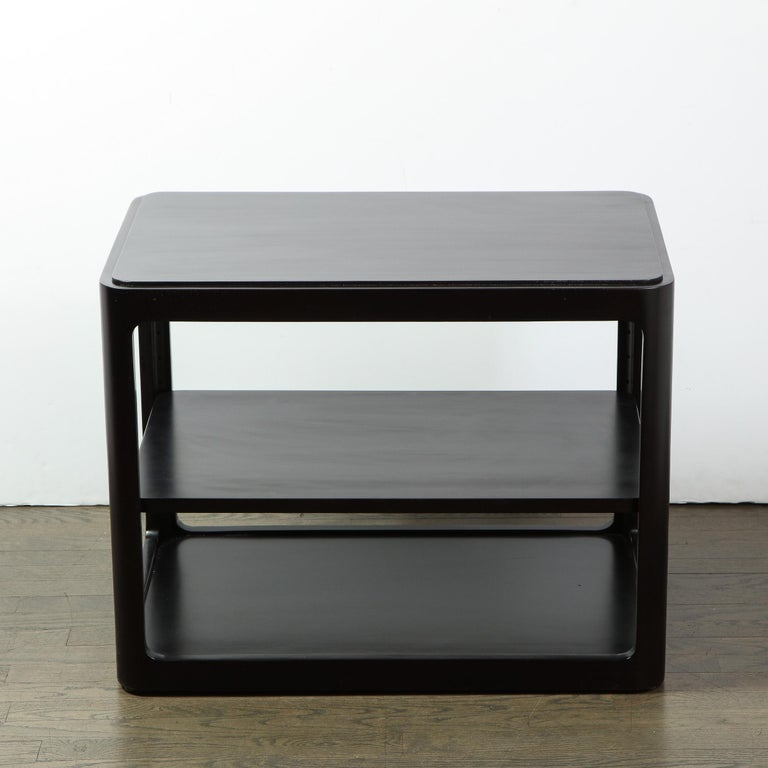This elegant Mid-Century Modern side/ end table was handcrafted in Berne, Indiana by the fabled American design firm Dunbar, circa 1960. It features a two-tier rectangular form with rounded corners and a subtly inset top- all finished in ebonized