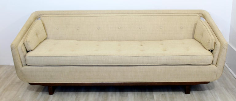 For your consideration is an elegant and sculptural sofa, in a raw silk blend, attributed to Dunbar or Laszlo, circa 1960s. In excellent vintage condition. The dimensions are 79.5