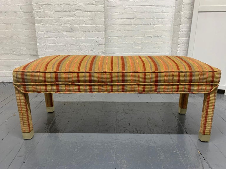Mid-Century Modern upholstered bench with brass-mounted feet.