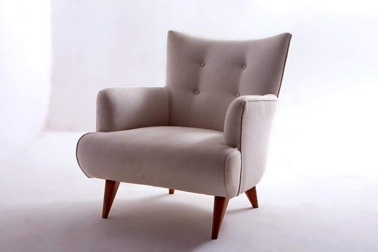 Mid-Century Modern upholstery lounge chair by Joaquim Tenreiro, Brazil 1956  Designed in 1956 in Brazil by the designer Joaquim Tenreiro, this lounge chair features splayed feet in solid peroba rosa wood and upholstery in natural ivory fabric.