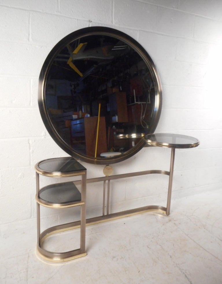 This stunning vintage modern vanity features a round swivel side table on one side with a smoked glass top. The sleek bent metal frame holds a large round mirror in the center with convenient two-tier shelving on one side. This unusual console has