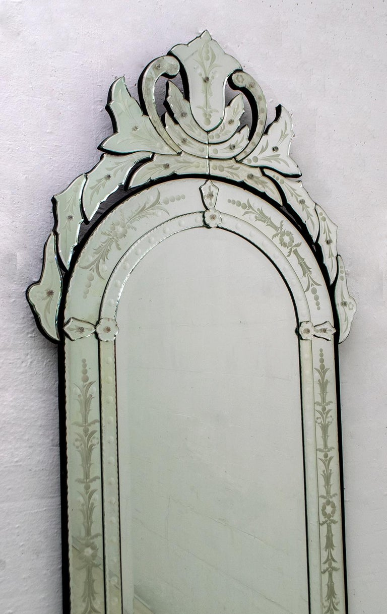 This elegant Mid-Century modern Venetian mirror was made in Italy, circa 1950. It features a cartouche shape with an arched panel and ground mirror in the center. There is a beveled chain around the edges and foliate details throughout. The top of