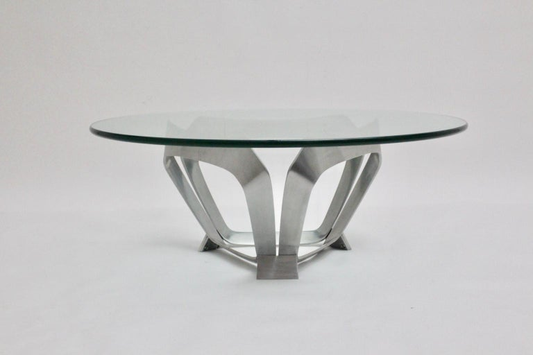 This presented Mid-Century Modern vintage coffee table was designed by Knut Hesterberg 1960s for Ronald Schmitt Germany. The coffee table shows an aluminum base in triangle shape with a clear glass plate with a thickness of 2 cm and polished