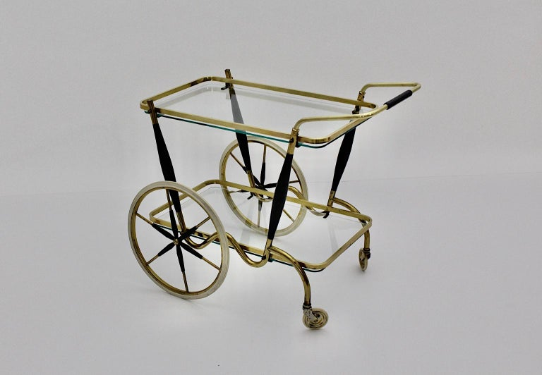 An elegant Mid-Century Modern two-tiered vintage brass cart, which was made out of brass and black lacquered beech. The bar cart features two small white rubber framed wheels and also two high spoke white rubber wheels, while two clear glass plates