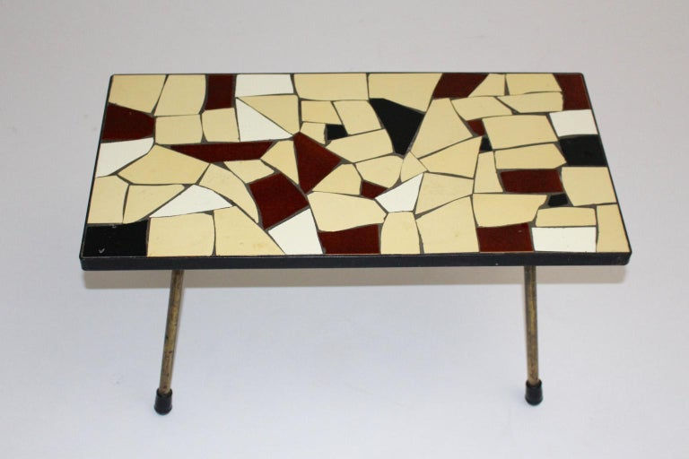 Mid Century Modern vintage sofa table or coffee table, which was designed and executed in Vienna circa 1950. While the coffee table shows a beautiful plate with ceramic tiles in the colors brown, ivory and white, the brass feet has black rubber