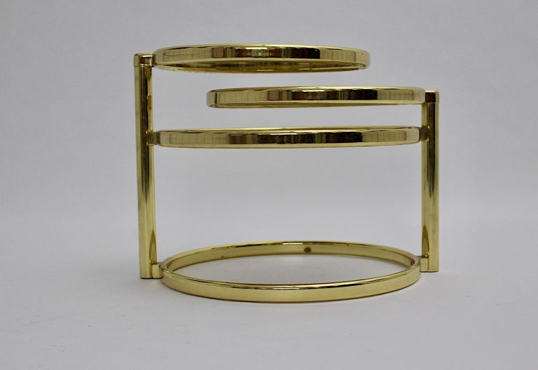 The Mid-Century Modern brassed metal and smoked glass coffee table shows two swiveling plates with the maximum width of 140 cm, if you unfold both plates.