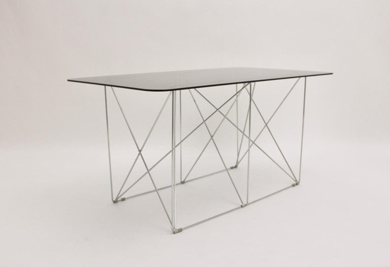 This fantastic foldable metal construction with a loose smoked glass plate ( thickness 0.8 cm ) was designed by Max Sauze, circa 1970, France. It is great to use as a dining table or as a writing table.