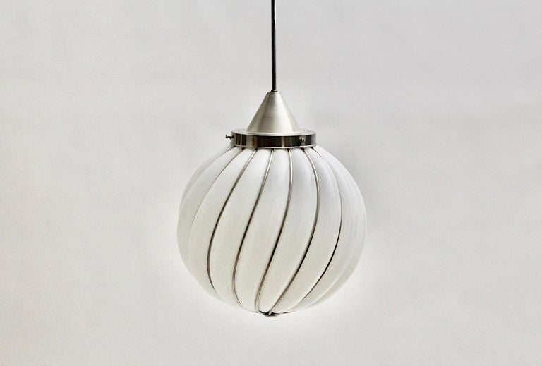 A Mid-Century Modern Vintage white glass nickel pendant or hanging lamp, which was designed and manufactured in Murano, Italy 1960s. The handmade and high-quality craftsmanship pendant features a white glass ball with nickel plated metal