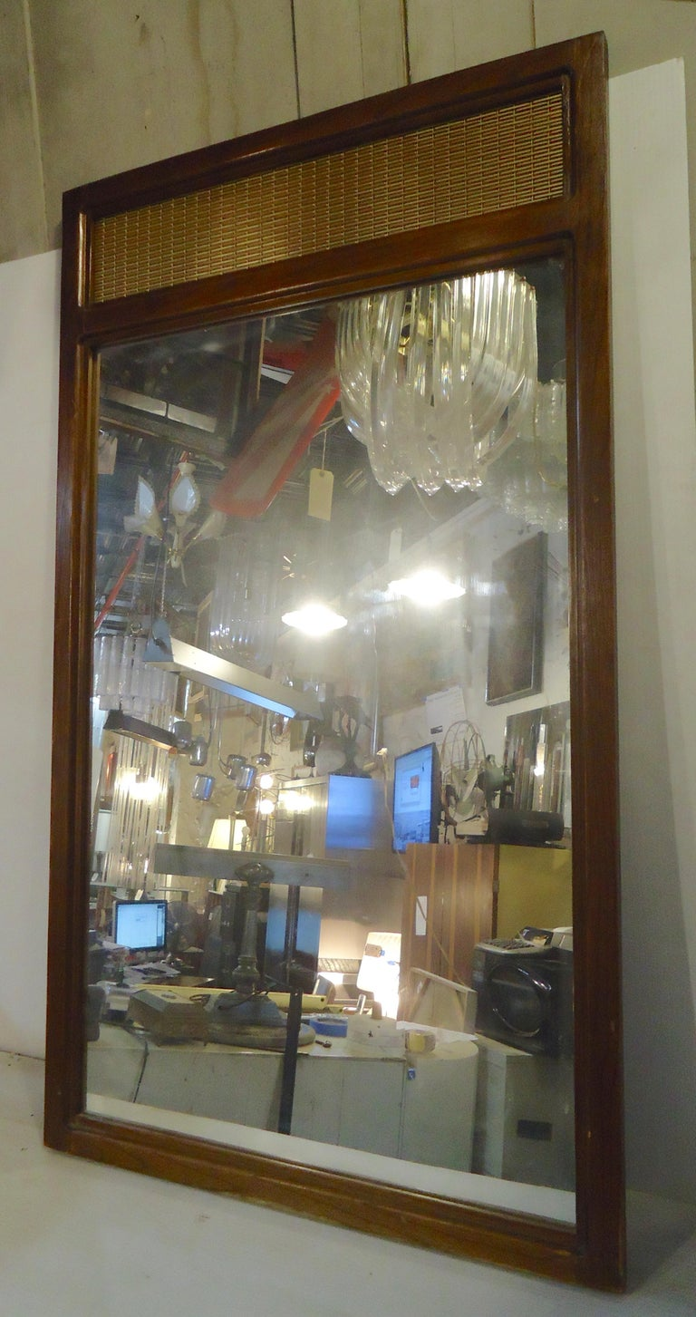 Tall vintage mirror with walnut trim and gold braided accent.