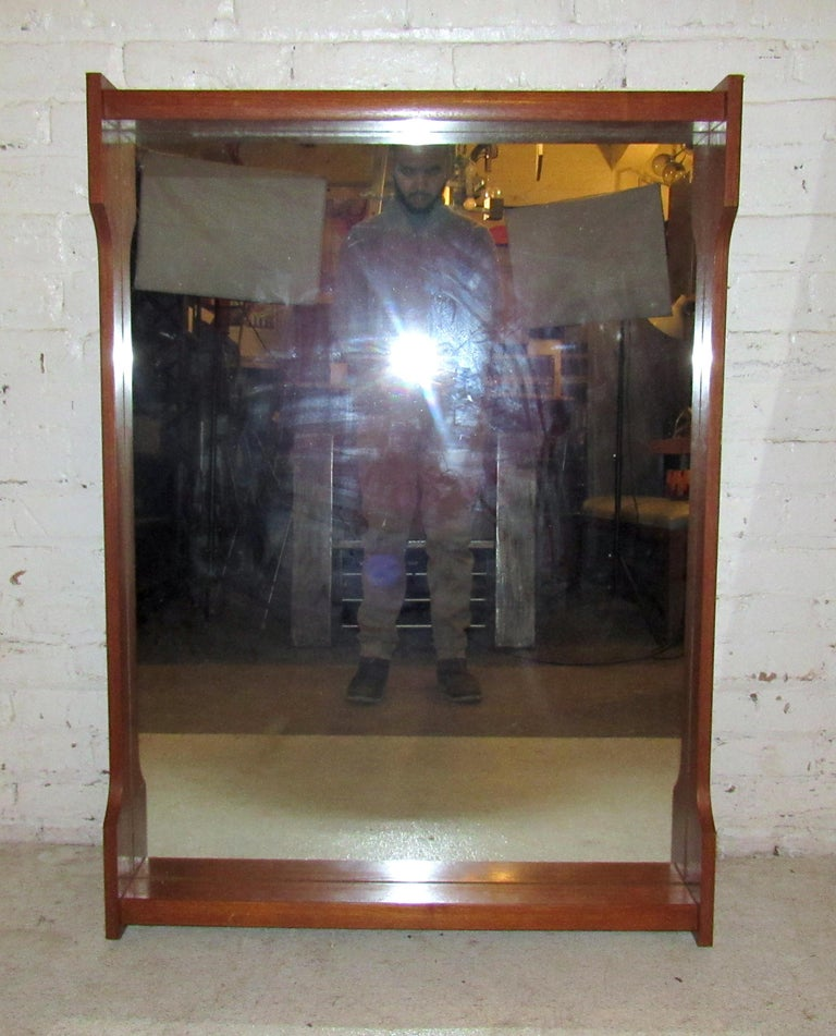 Sleek vintage modern wall mirror featuring a small shelf, stamped RS.  (Please confirm item location - NY or NJ - with dealer).