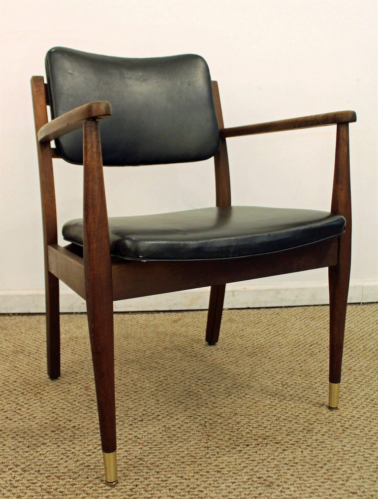 This open-armchair has a walnut frame, brass feet, and vinyl upholstery, in good condition for its age. It was made by Gregson Manufacturing Co.  Measure: 24