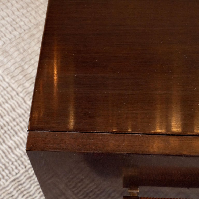 This refined and elegant Mid-Century Modern sideboard was designed by the celebrated T.H. Robsjohn Gibbings and handmade in Grand Rapids, Michigan, circa 1950. Sitting on conical brass legs with circular bases, this stunning rectilinear sideboard
