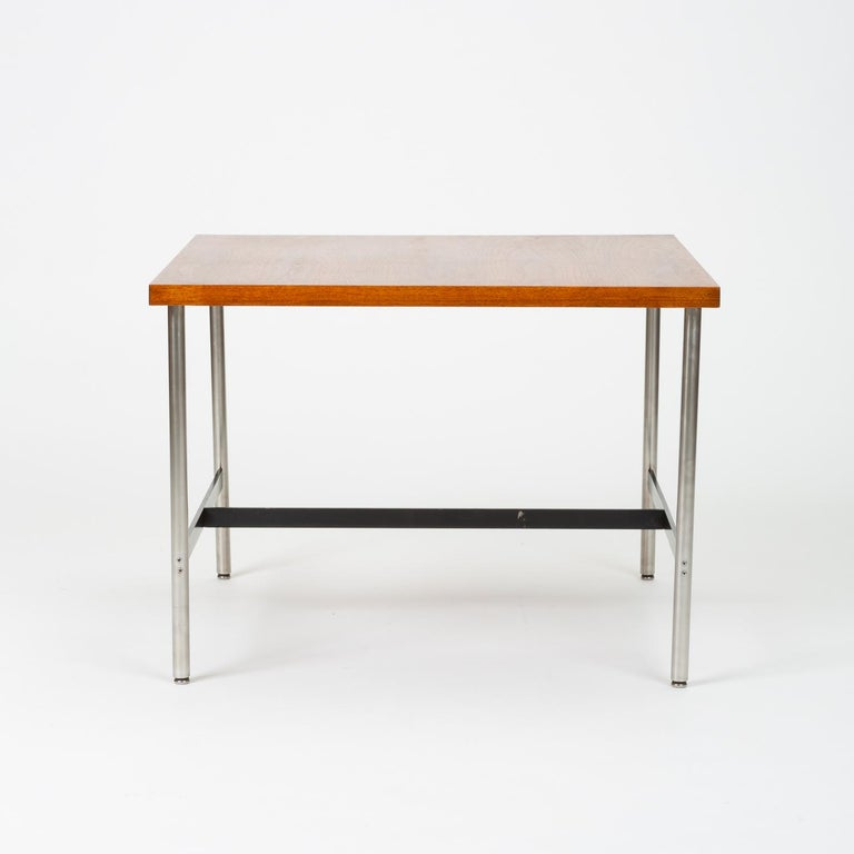 A modernist children's table by Herman Miller with a square tabletop and metal frame. Four round legs of brushed steel with steel glides sit slightly inset from the corners of the work surface. An I-shaped metal support in black-enameled steel joins