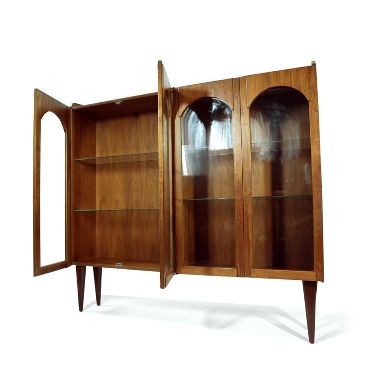 Handsome Mid-Century Modern walnut wood china cabinet with novel arched facade. This four bay china cabinet features four glass shelves inside. Reposition the shelves as you wish to create the perfect display for your cherished collectibles or