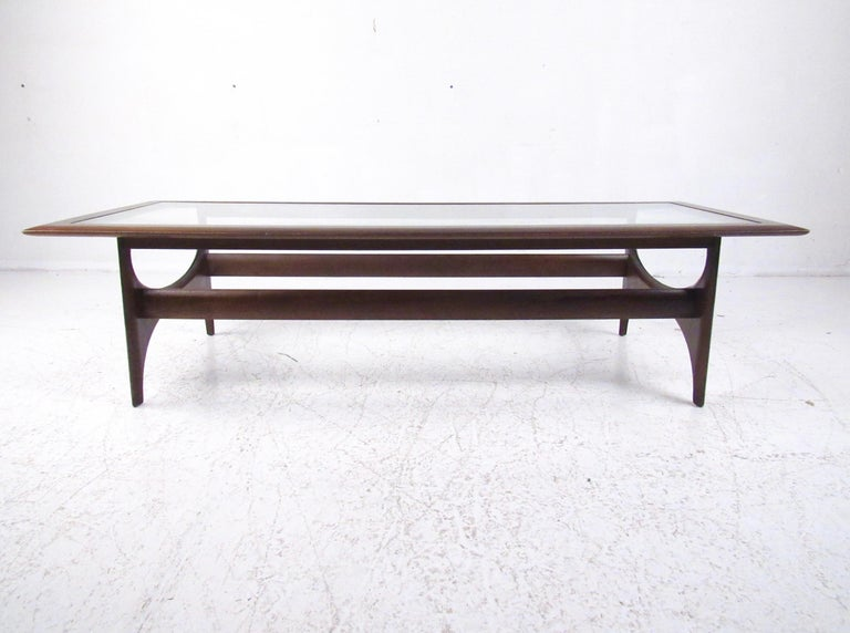 This striking walnut finish coffee table features a glass top and stylish Mid-Century Modern design. Simple yet unique design by Lane Furniture makes an impressive centre table for home or business seating arrangement. Please confirm item location