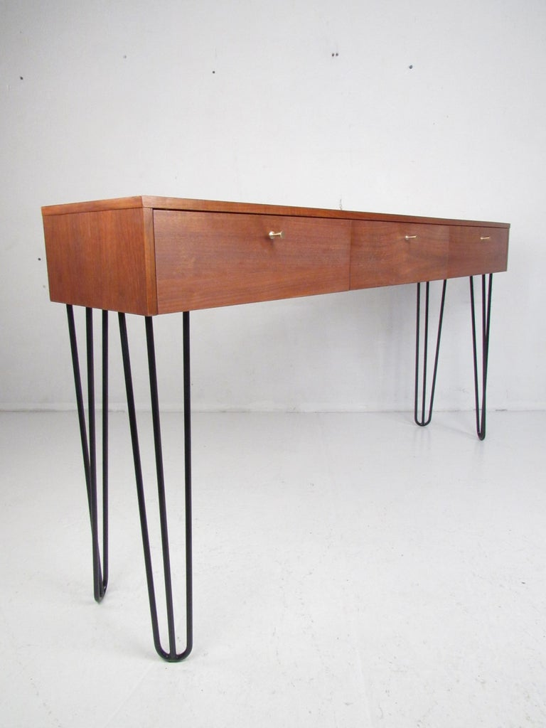 This versatile midcentury vanity features three drop front storage compartments and large metal hairpin legs. A stylish piece that functions as a small desk, vanity, or a hall table. This lovely vintage modern table looks great in any bedroom,