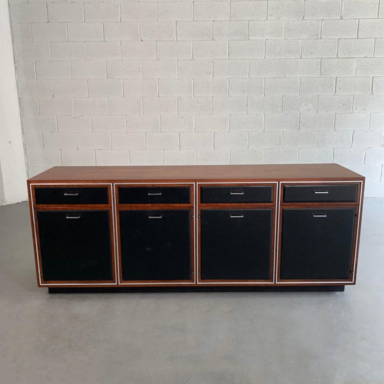 Mid-Century Modern credenza by John Stuart features a crotch walnut surround and vinyl covered drawer and door fronts with aluminum trim and handles. The bottom cabinets are 18 W x 18 D x 19 H.