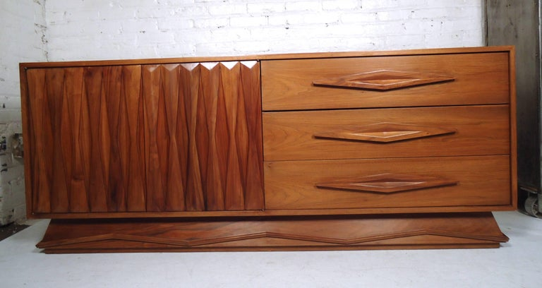 Vintage modern walnut credenza featuring many sculpted wood detail throughout, three drawers and a spacious storage compartment.