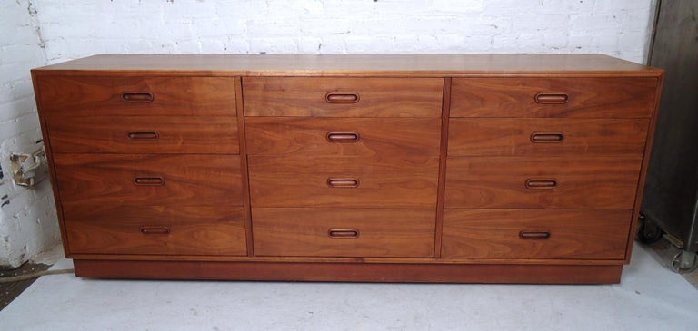 Vintage modern 12 drawer credenza featuring rich walnut grain, sculpted pulls, and a sturdy base.  Please confirm item location (NY or NJ) with dealer.